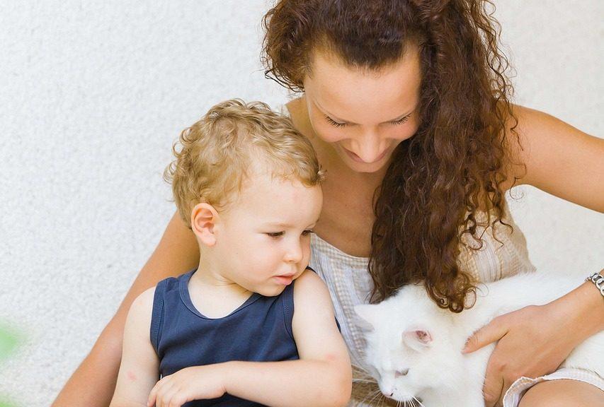 Frau mit Kind und weißer Katze